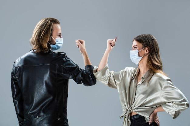 Coronavirus quarantäne. ellbogen stoßen. zwei leute stoßen an die ellbogen. coronavirus epidemie. freunde in sicherheitsmaske. junges paar trägt gesichtsmasken. mädchen und kerl grüßen mit ellbogen. neues reales leben