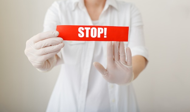 Coronavirus-quarantäne, rotes warnschild mit text stop, arzt zeigt stop-hand-geste für stop-corona-virus-ausbruch