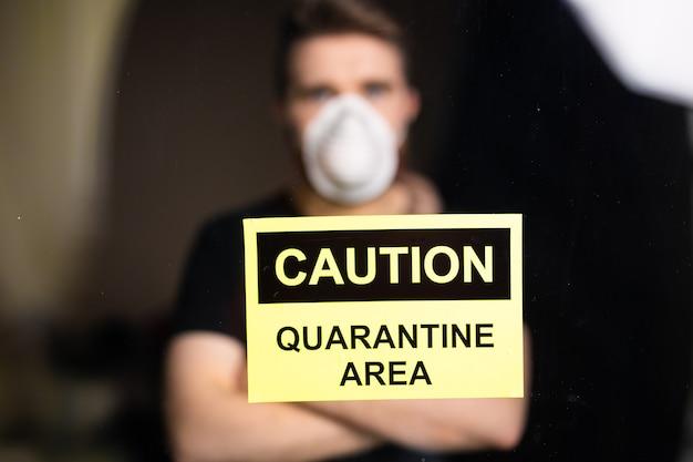 Coronavirus-, quarantäne- und pandemiekonzept. trauriger und kranker mann des koronavirus, der durch das fenster schaut