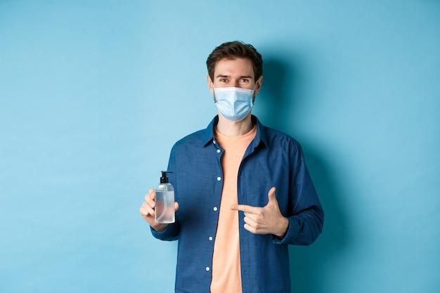 Coronavirus, quarantäne und soziales distanzierungskonzept. glücklicher junger mann in der medizinischen maske, die flasche des händedesinfektionsmittels empfiehlt, auf antiseptisch und lächelnd, blauer hintergrund zeigend.