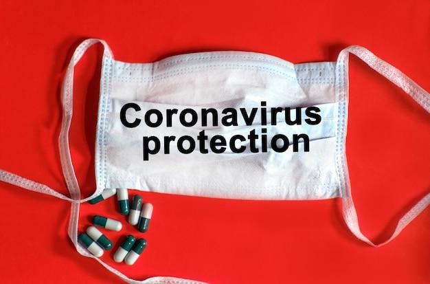 Coronavirus-schutz - text auf einer schützenden gesichtsmaske, tabletten auf rotem hintergrund