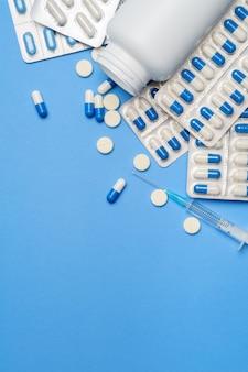 Coronavirus-schutzkonzept - pillen, kapseln, tabletten und spritze auf blauem hintergrund