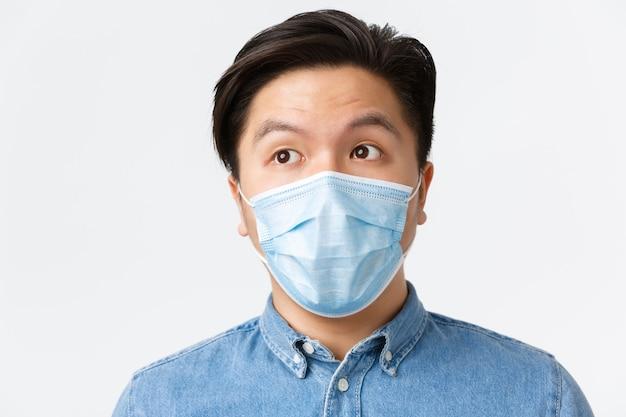 Coronavirus, soziale distanzierung und lifestyle-konzept. nahaufnahme eines nachdenklichen asiatischen männlichen unternehmers in medizinischer maske, der in der oberen linken ecke nachdenkt, die wahl trifft, weißer hintergrund.