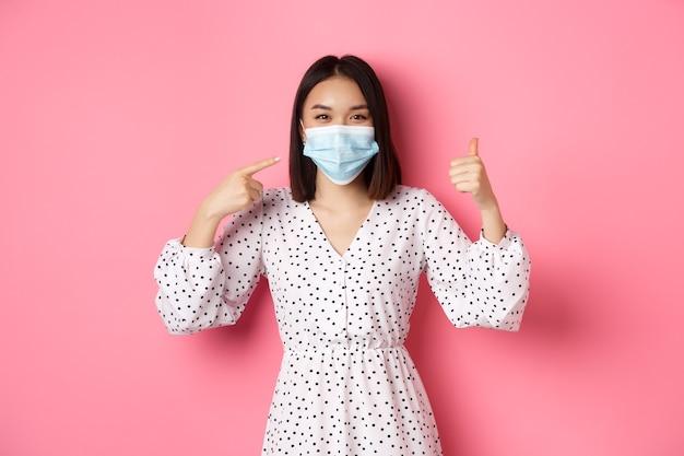 Coronavirus soziale distanzierung und lifestyle-konzept süße asiatische frau, die auf gesichtsmaske zeigt, die t ...