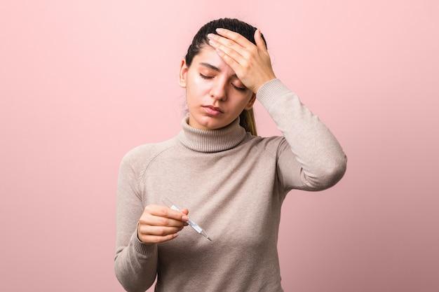 Coronavirus-symptome. frau mit fieber und kopfschmerzen, die thermometer halten, das verzweifelt gegen blauen hintergrund schaut