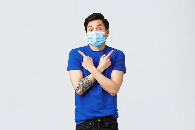 Coronavirus und lifestyle-konzept. unentschlossener und ahnungsloser junger asiatischer mann, der seitlich nach links und rechts zeigt und um rat fragt, was er wählen soll
