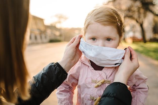 Coronavirus- und luftverschmutzungskonzept. kleines mädchen und mutter, die masken tragen, gehen auf straße. mutter korrigiert maskenkind. symptome des pandemievirus. familie mit kind im freien. krankheitsschutz.