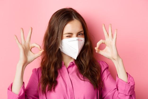 Coronavirus, vorbeugende maßnahmen und gesundheitskonzept. fröhliches mädchen zwinkert, trägt atemschutzmaske, zeigt gute zeichen, lobt gute wahl, gut gemachte geste, rosa wand.