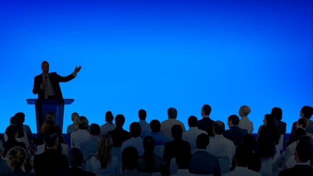 Corporate businessman hält eine präsentation vor einem großen publikum