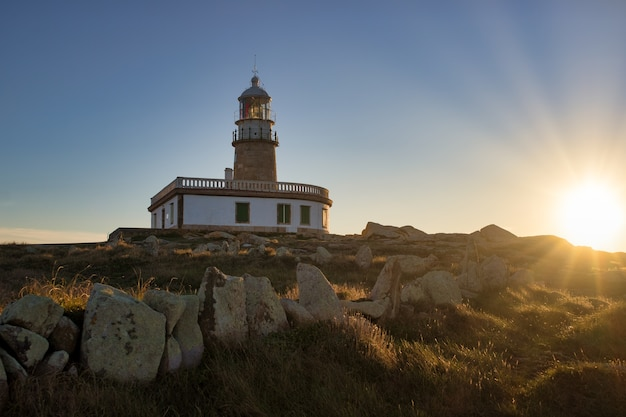 Corrubedo leuchtturm umgeben von felsen und gras unter dem sonnenlicht in spanien