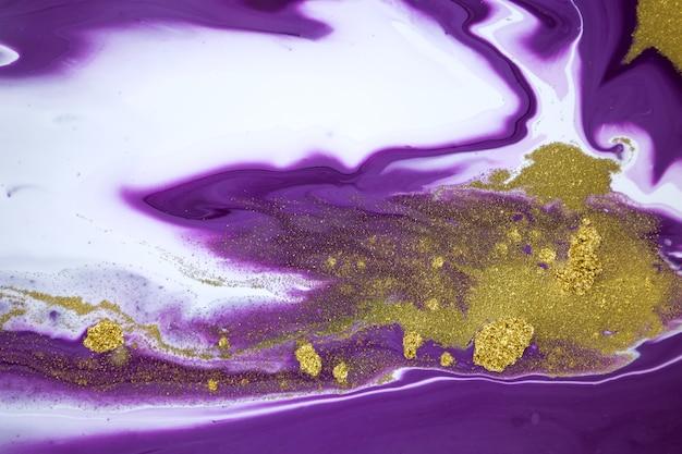 Cose herauf goldglitter auf flüssigem gemischtem lila tintenhintergrund.