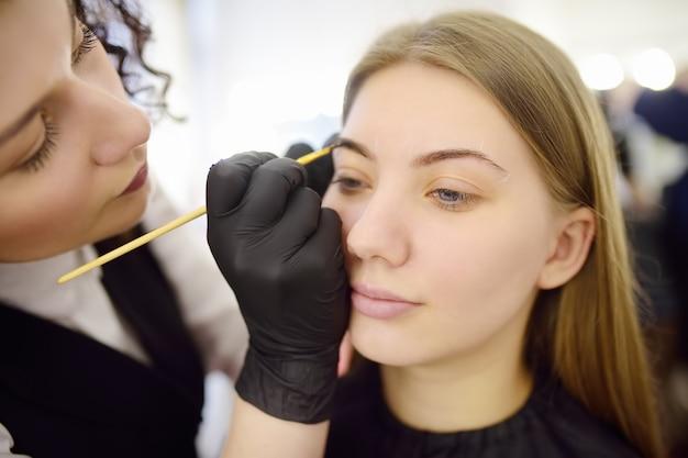 Cosmetologist, der augenbrauen durch pinsel malt.