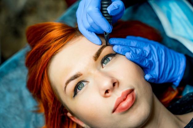 Cosmetologist, der dauerhaftes make-up auf augenbrauen - augenbrauentätowierung anwendet