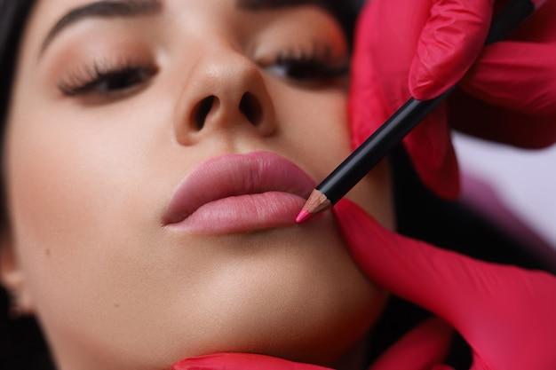 Cosmetologist, der dauerhaftes make-up auf dem gesicht der frau macht