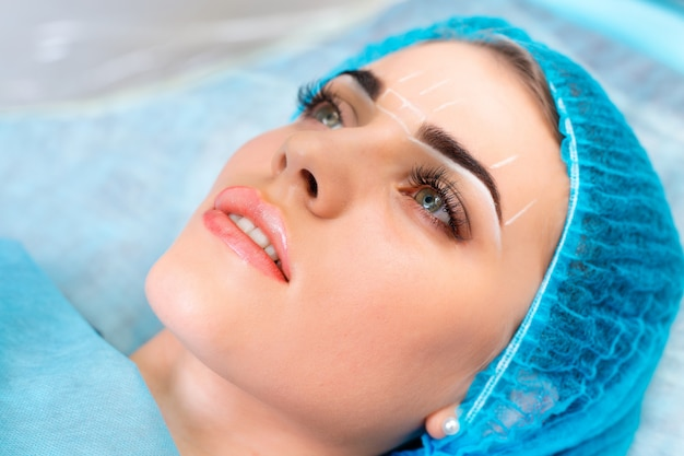 Cosmetologist, der dauerhaftes make-up auf frauengesicht macht