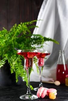 Cosmopolitan oder margarita-cocktail, garniert mit makronen und beeren