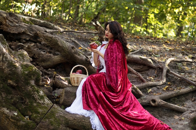Cosplay zum märchen schneewittchen, eine frau in einem roten umhang und einen karren mit äpfeln im wald