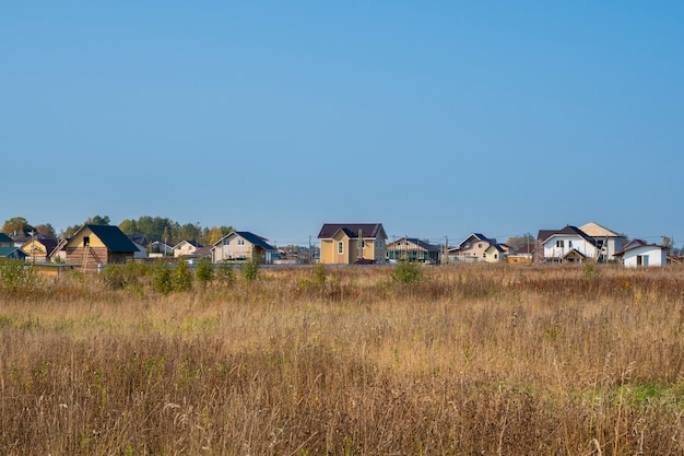 Cottage dorf. herbstansicht eines modernen häuschendorfes in einem trockenen gelben feld. russland.