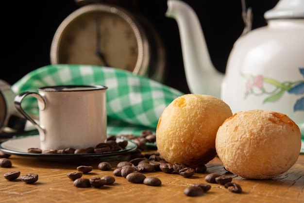 Couchtisch in brasilien im detail mit antiker uhr, tassen, kaffeebohnen und käsebrot auf rustikalem holz, mit grün-weiß karierter tischdecke, selektiver fokus.