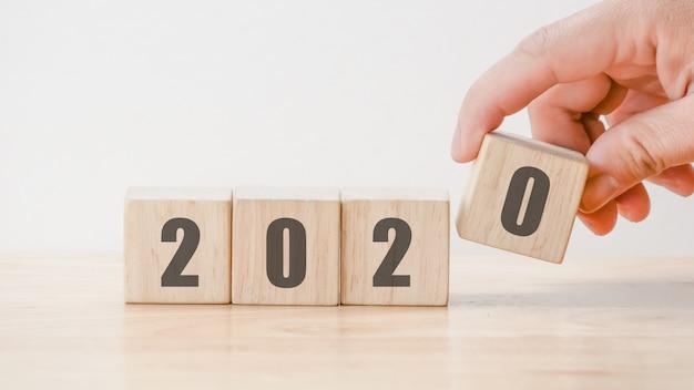 Count-down-konzept des entwurfes des neuen jahres 2020, hand, die würfel der hölzernen blöcke auf holztischhintergrund hält