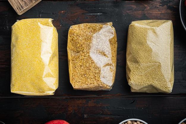 Couscous, bulgur und polenta im sprung, draufsicht auf dunklem holztisch.