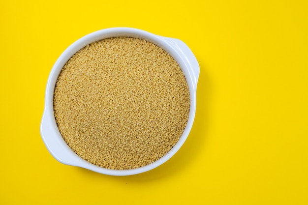 Couscous in der weißen schüssel auf gelbem papierhintergrund