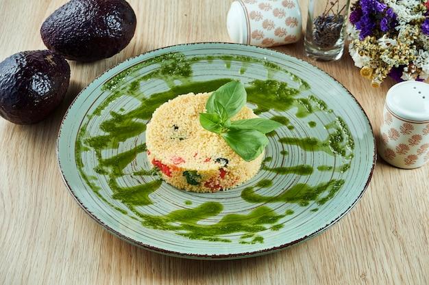 Couscous mit tomaten, pesto und basilikum auf einem blauen teller auf einem holztisch. gesundes vegetarisches essen. fitness ernährung. nahaufnahme.