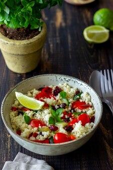 Couscous-salat mit tomaten, paprika, zucchini und preiselbeeren. vegetarisches essen. diät. gesundes essen.