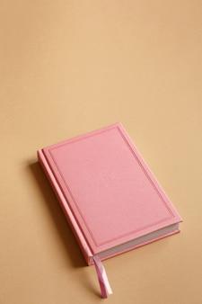 Cover von rosa notizbuch, tagebuch oder buch auf braunem papier