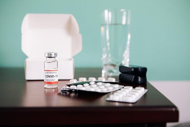 Covid-19 ampullen mit impfstoff und pillen auf einem tisch. gesundheitswesen und medizinisches konzept.