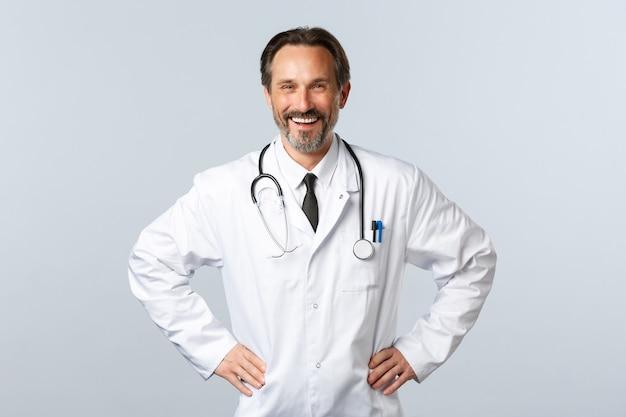 Covid-19, coronavirus-ausbruch, gesundheitspersonal und pandemiekonzept. begeisterter lächelnder männlicher arzt freut sich, patienten zu helfen. arzt im weißen kittel glücklich bei der arbeit in der klinik oder im krankenhaus