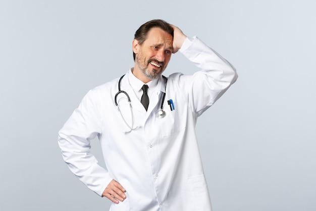 Covid-19, coronavirus-ausbruch, gesundheitspersonal und pandemiekonzept. beunruhigter und besorgter, verzweifelter männlicher arzt im weißen kittel, der den kopf berührt und das gesicht verzieht, schauen betrübt weg