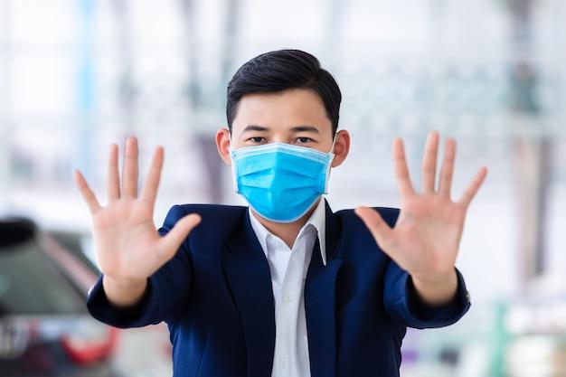 [covid-19] coronavirus concept.man trägt eine maske zum schutz von pm2.5 und zeigt eine handbewegung zum stoppen des covid-19-ausbruchs. symptome des coronavirus und des epidemischen virus.