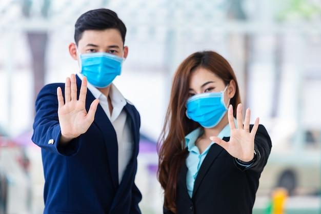 [covid-19] coronavirus-konzept. mann und frau tragen eine maske zum schutz von pm2.5 und zeigen eine handbewegung zum stoppen des covid-19-ausbruchs. symptome des coronavirus und des epidemischen virus.