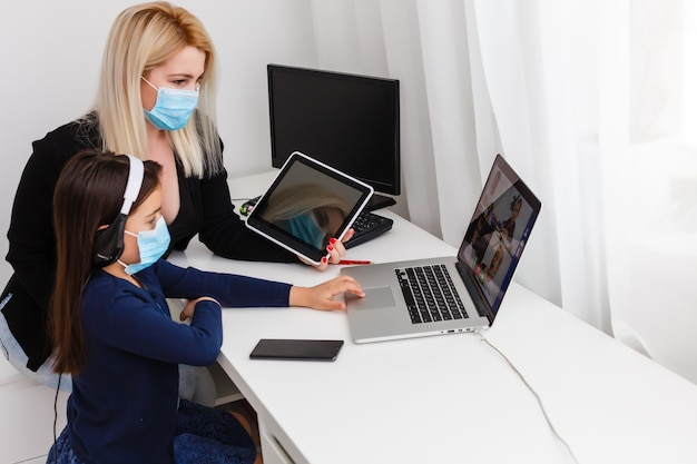 Covid-19 coronavirus und lernen von zu hause, konzept für heimschulkinder. kleines mädchen online-lernen mit mutter von zu hause aus. quarantäne- und social distancing-konzept.