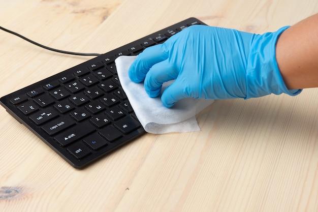 Covid-19 desinfektion von büroräumen durch abwischen des coronavirus, reinigung und desinfektion ihres arbeitsplatzes. desinfektionstücher zum abwischen der oberfläche von schreibtisch, tastatur, maus.