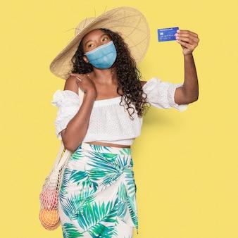 Covid 19, frau in medizinischer maske, die eine kreditkarte hält