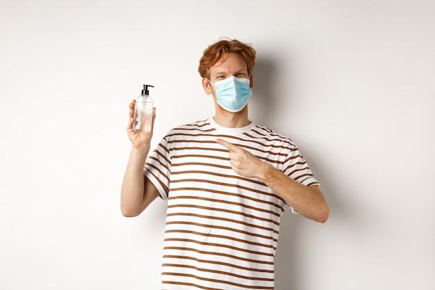 Covid-19, gesundheits- und lifestyle-konzept. fröhlicher rothaariger mit gesichtsmaske, der mit dem finger auf handdesinfektionsmittel zeigt und antiseptischen, weißen hintergrund empfiehlt.
