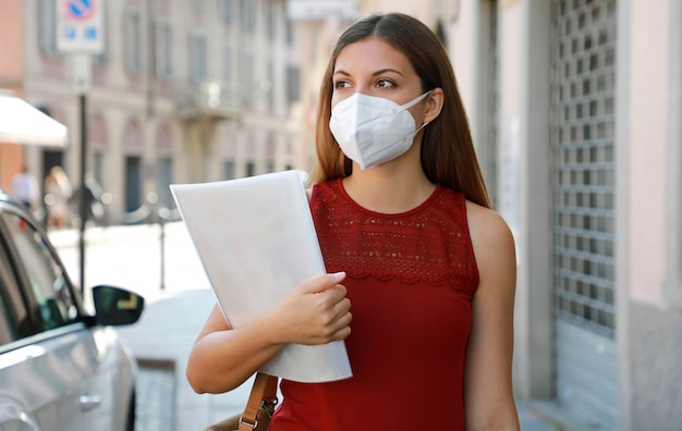 Covid-19 globale wirtschaftskrise arbeitslose frau mit maske, die ein mobiltelefon benutzt und lebenslauf liefert