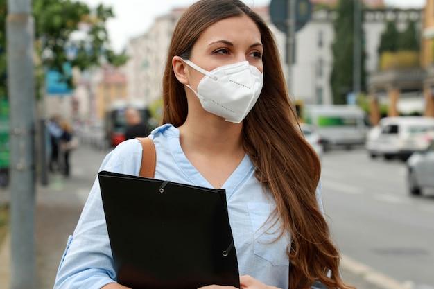 Covid-19 globale wirtschaftskrise arbeitsloses besorgtes mädchen mit maske auf der suche nach einem job in der stadtstraße mit lebenslauf
