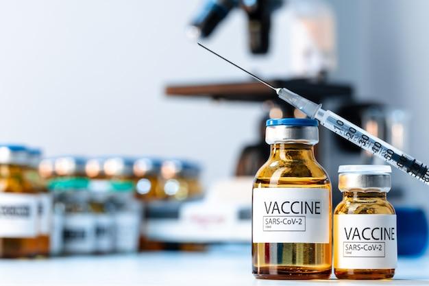Covid-19-impfflasche mit einer spritze auf dem labortisch