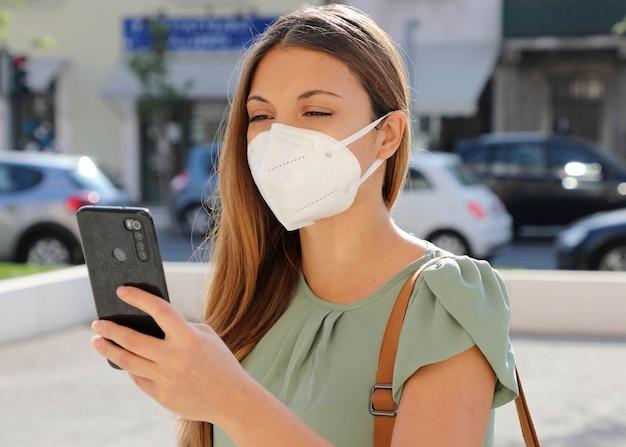 Covid-19 junge frau, die ffp2-maske mit smartphone in der stadtstraße trägt