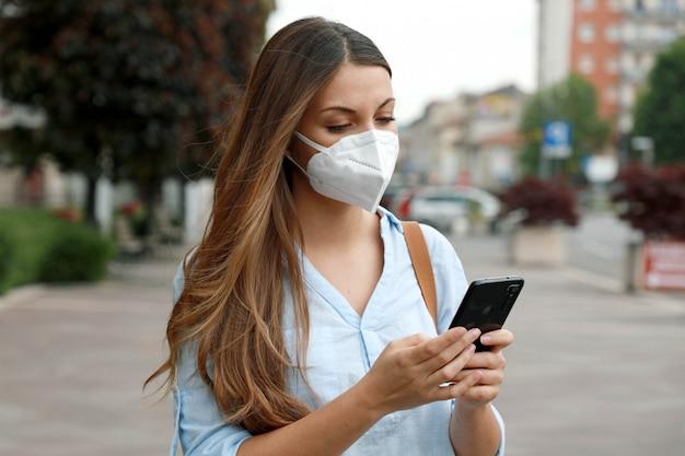 Covid-19 junge frau trägt ffp2-maske mit smartphone-anwendungssoftware in der city street