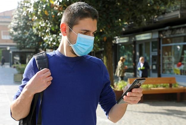 Covid-19 junger mann, der ffp2-maske mit smartphone in der stadtstraße trägt