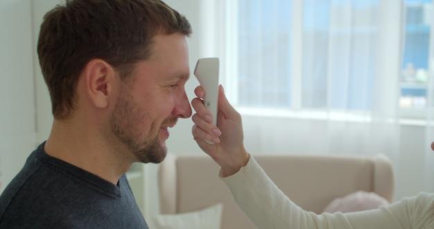 Covid-19 körpertemperaturmessung für coronavirus. die temperatur eines mannes wird zur kontrolle der krankheit gemessen.