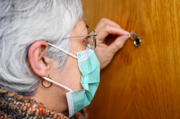 Covid-19-konzept. bleib zuhause. selbstisolation zur verhinderung der coronavirus-pandemie. ältere frau in schützender grüner maske schaut durch das guckloch.