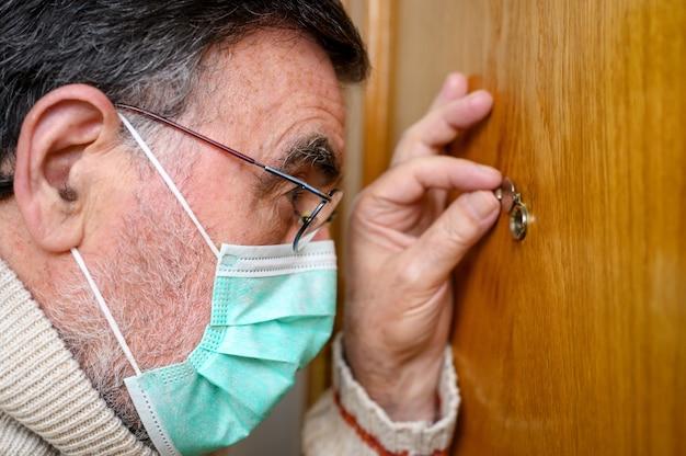 Covid-19-konzept. bleib zuhause. selbstisolation zur verhinderung der coronavirus-pandemie. älterer mann in schützender grüner maske schaut durch das guckloch.
