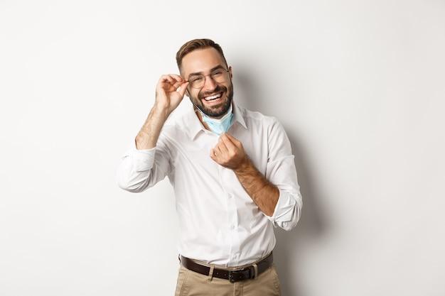 Covid-19, konzept der sozialen distanzierung und quarantäne. glücklicher geschäftsmann zieht gesichtsmaske aus und lächelt, stehend auf weißem hintergrund.