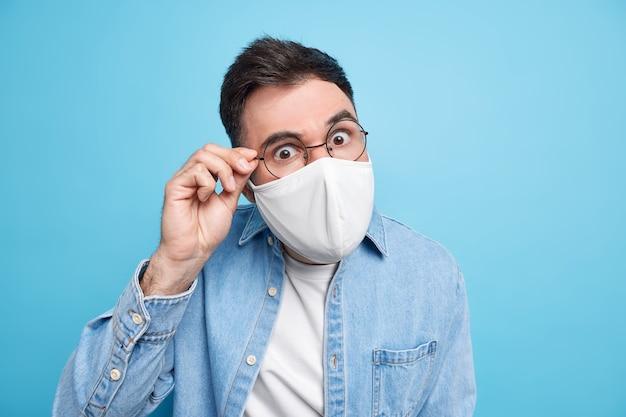 Covid-19-konzept. ernsthafter aufmerksamer erwachsener mann sieht durch eine brille, trägt eine schützende gesichtsmaske und bittet darum, die regeln der sozialen distanzierung in jeanshemd zu befolgen