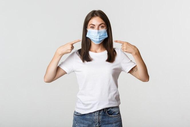 Covid-19, konzept für gesundheit und soziale distanzierung. attraktives brünettes mädchen in der medizinischen maske, die finger auf gesicht zeigt, weiß.